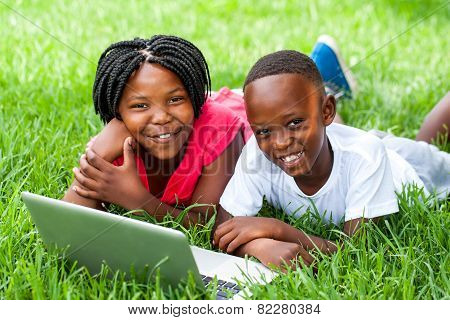 Two African Kids Laying On Grass With Laptop.