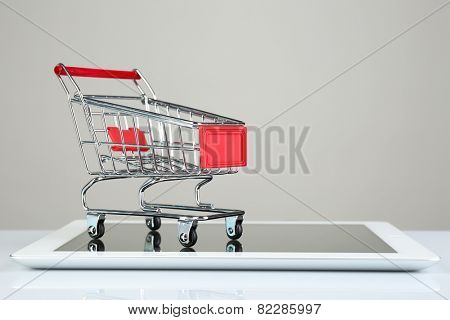 Tablet with small shopping cart isolated on white background
