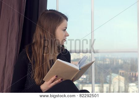 Woman At Home And Looking Through The Window