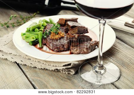 Steak on plate with bottle of wine on wooden background