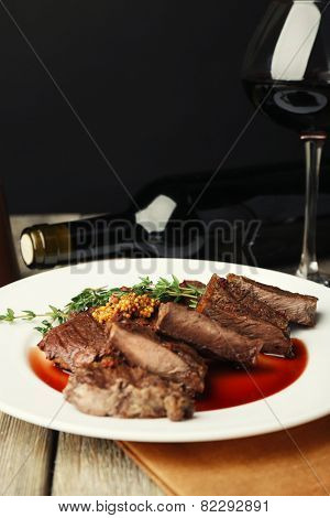 Steak with wine sauce on plate and bottle of wine on dark background