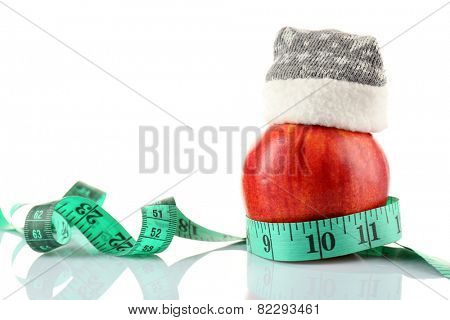 Measuring tape and apple with Christmas decoration isolated on white