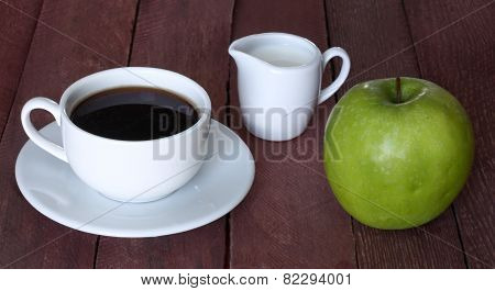 Coffee cup, the milk jug and apple