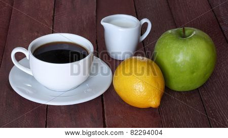 Coffee cup, the milk jug and fruit