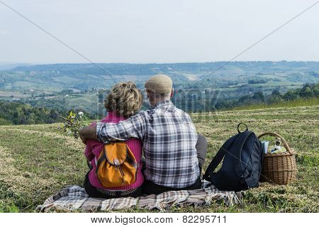 Senior Couple Sitting In The Field