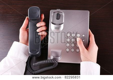 Female hand holding phone receiver and dialing number on wooden background