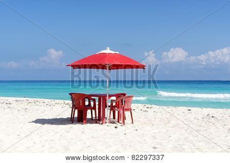 Chairs, table and umbrella on a tropical beach in Cancun, Mexico.