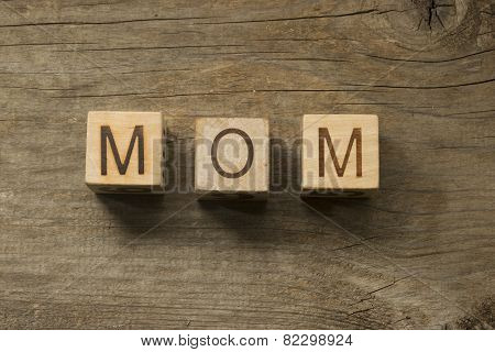 Word MOM on the child blocks on a wooden background