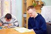 stock photo of daycare  - young adult man engages in self study in rehabilitation center - JPG