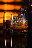picture of whiskey  - whiskey and ice on a glass table - JPG