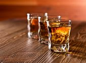 picture of whiskey  - whiskey and natural ice on old wooden table - JPG