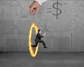 stock photo of juggler  - Businessman jumping through fire circle hand holding with doodles wall background - JPG