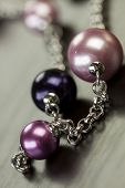 foto of handicrafts  - Close up of three attractive shiny purple beads attached by silver chains on an item of jewellery in a fashion and handicraft concept - JPG