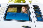 pic of limousine  - Bride looks out of the window a white limousine - JPG