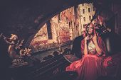 stock photo of carnival ride  - Beautiful woman in red cloak riding on gondola - JPG