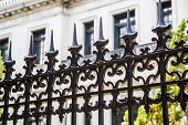 pic of spike  - Old ornamental wrought iron fence with spiked tops in front of stone building - JPG