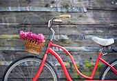foto of wooden basket  - Vintage bicycle with basket with peony flowers near the old wooden wall - JPG