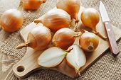 image of cutting board  - Fresh onions on a cutting board on the kitchen table - JPG