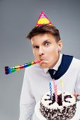 image of office party  - Funny close up picture of young office manager with party hat and blower - JPG