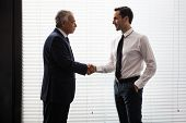 stock photo of 55-60 years old  - Half length portrait of two businessmen standing up and shaking hands - JPG