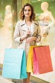 pic of shopping center  - Beauty woman with shopping bags in shopping mall is looking at the camera - JPG