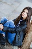 pic of straight jacket  - Beautiful young girl, Caucasian appearance, with dark, long, straight hair, brown eyes and beautiful dark eyebrows, wearing a striped shirt, blue jeans and black leather jacket, sitting on the street on the sidewalk