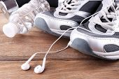 image of bottles  - Sport shoes and bottle of water on wooden background - JPG