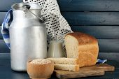 stock photo of milk products  - Retro can for milk with fresh bread and glass jug of milk on wooden background - JPG