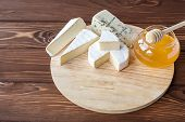 stock photo of brie cheese  - cheese plate with Brie Camembert Roquefort on wooden plate - JPG