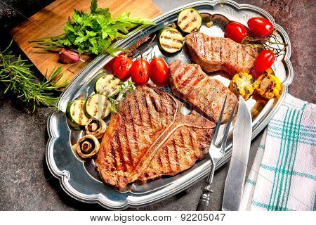 Grilled beef steaks with vegetables on platter