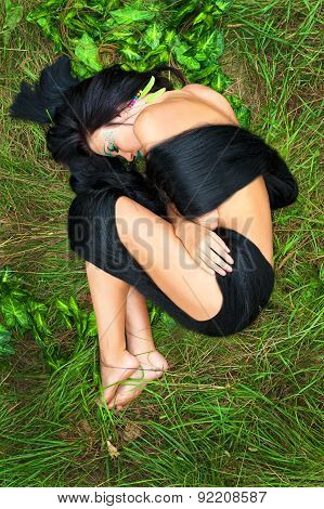 beautiful woman with long black hair lying on green grass