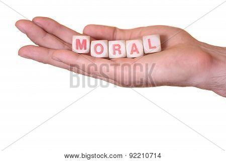 Moral Written With Wooden Dice On A Hand, Isolated On White Background