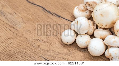 Champignons Mushrooms On Wooden Tabletop. Space For Your Text.