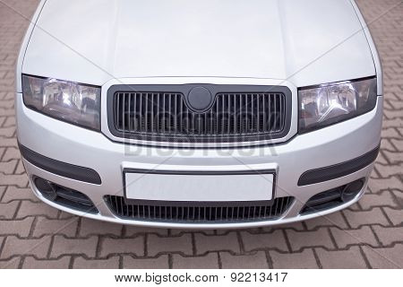 Close-up photo of front part the silver car