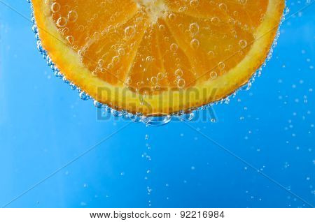 Fresh Orange Slice In Sparkling Blue Water