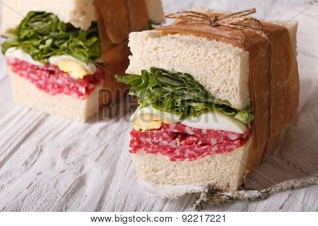 Sandwiches With Salami And Egg Wrapped In Paper