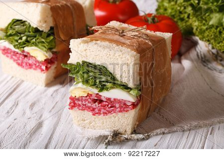 Sandwiches With Salami Wrapped In Paper Close-up Horizontal