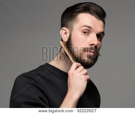 young man comb his beard and moustache