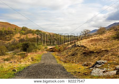 Rural Gravel Road In Scottish Highlands, West Highland Way. Beautiful Cloudy Sky