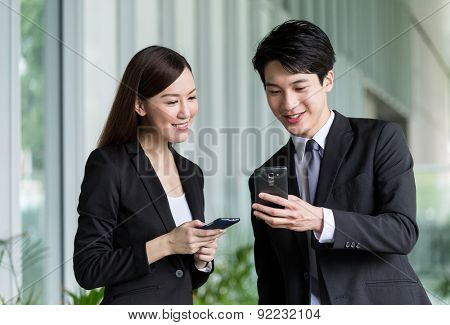 Business partner discuss about the detail on smartphone