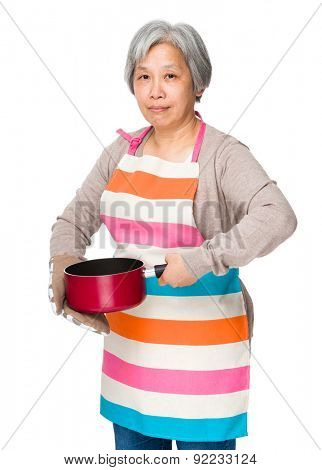 Elderly housewife holding with saucepan
