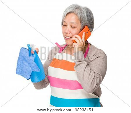Asian old housewife talk to cellphone and usinf rag and bottle spray