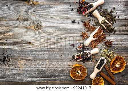 odorous dry teas in scoops on wooden background