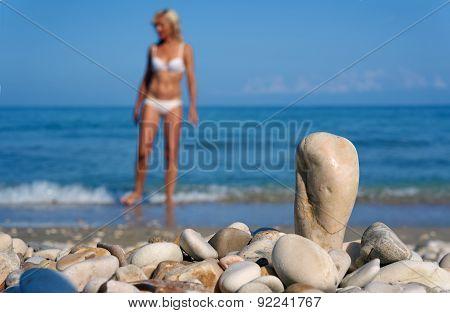 Pebbles and girl in a bikini on a beach