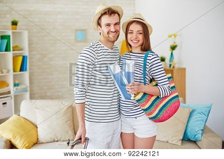 Amorous and happy couple with airtickets looking at camera