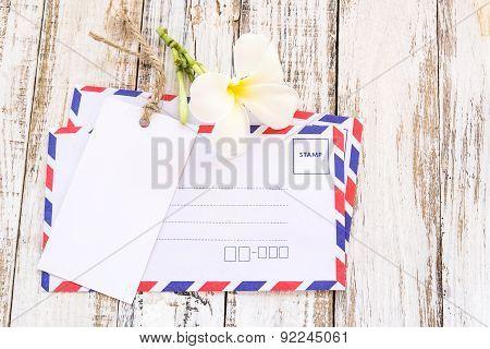 Envelope, Plumeria And White Card On White Wooden Table