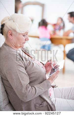 Side view of senior woman using digital tablet at home