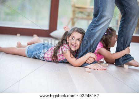 Low section of father dragging girls on hardwood floor