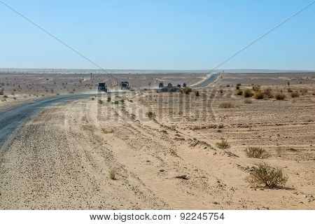 Convoy Of 4X4 Vehicle Drive A Dusty Desert Track In Tunisia