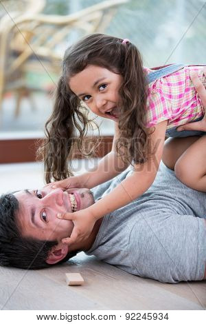 Mischievous daughter on top of father at home